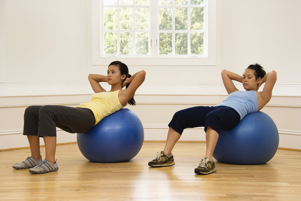 Women doing exercise ball workouts at home